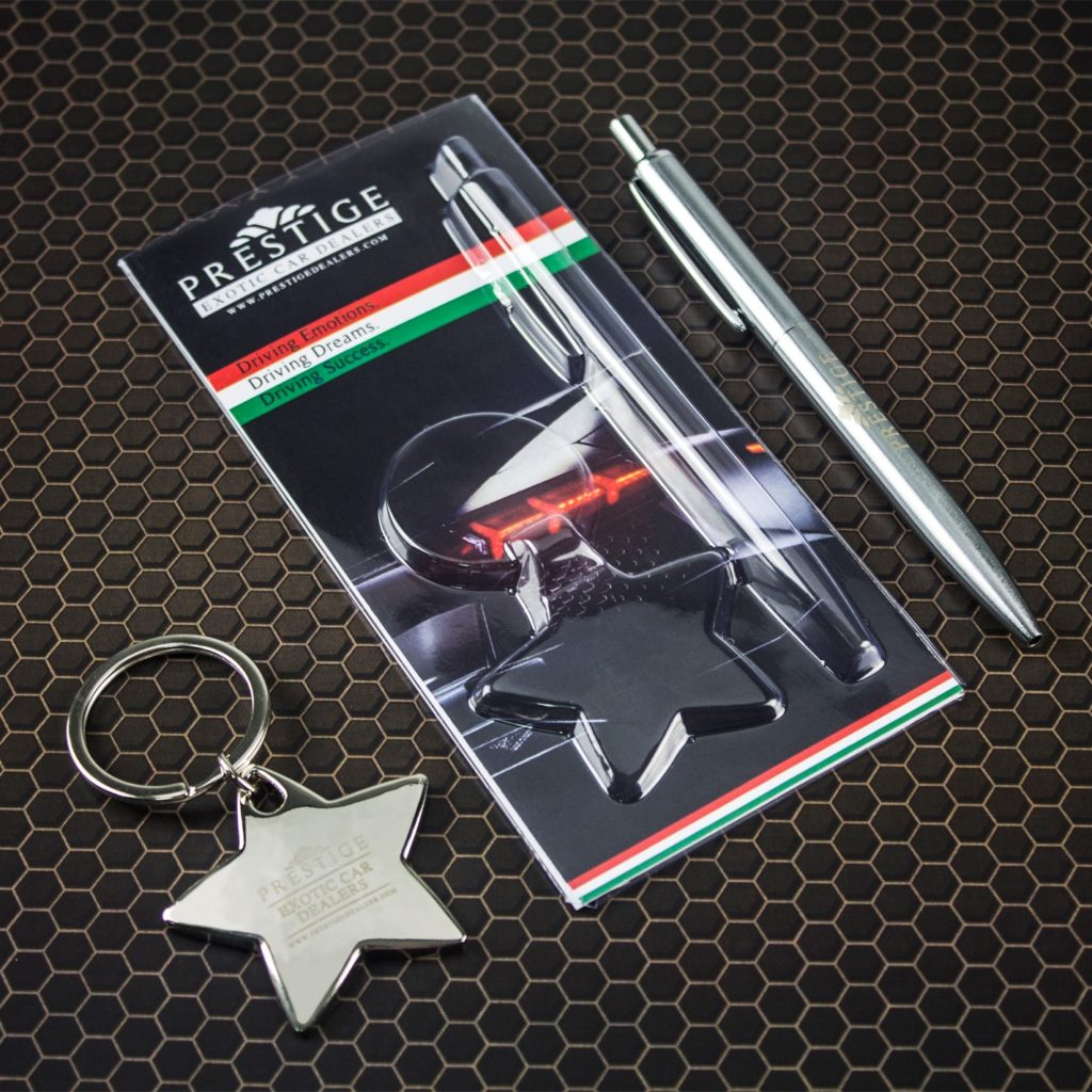 Photo of engraved silver keyring and silver pen set on black background