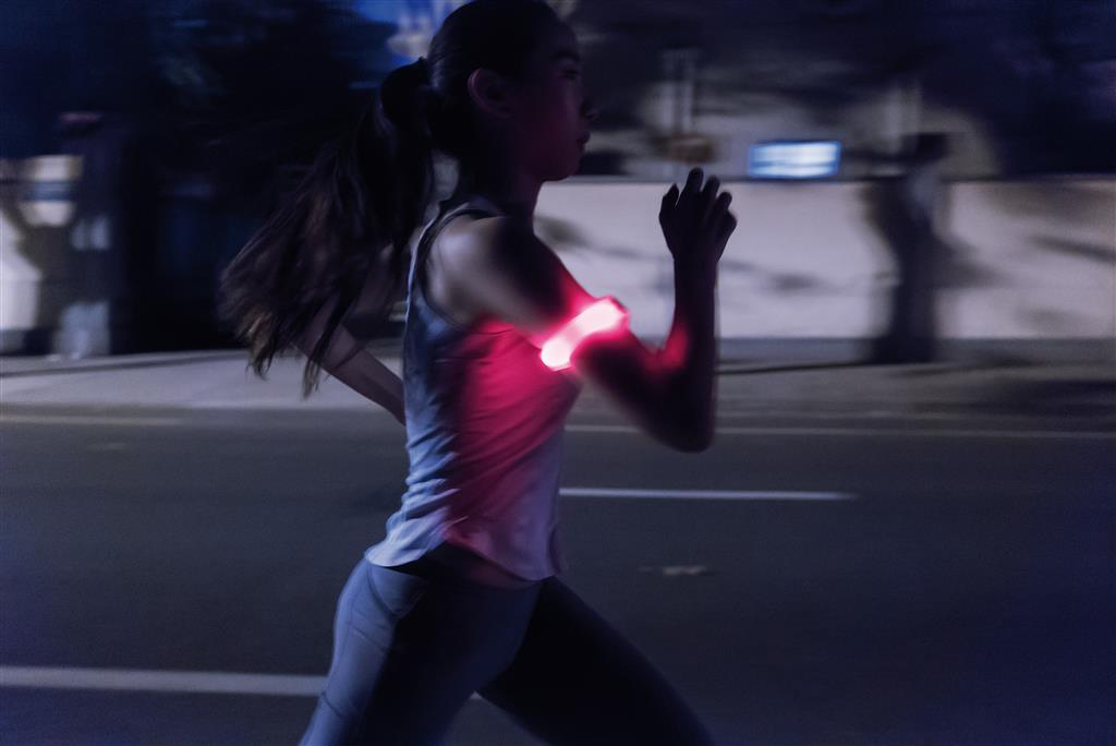 photo of woman running at night using the safety running LED band